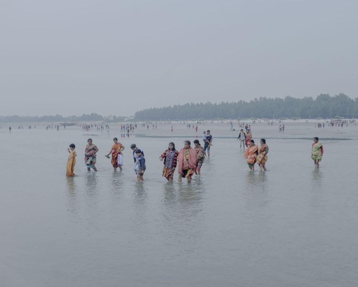 Mulheres e crianças atravessam águas pouco profundas.