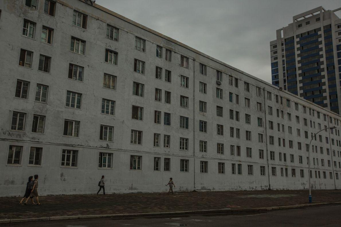 Pessoas que se deslocam diariamente, em frente a um bloco de apartamentos de Pyongyang
