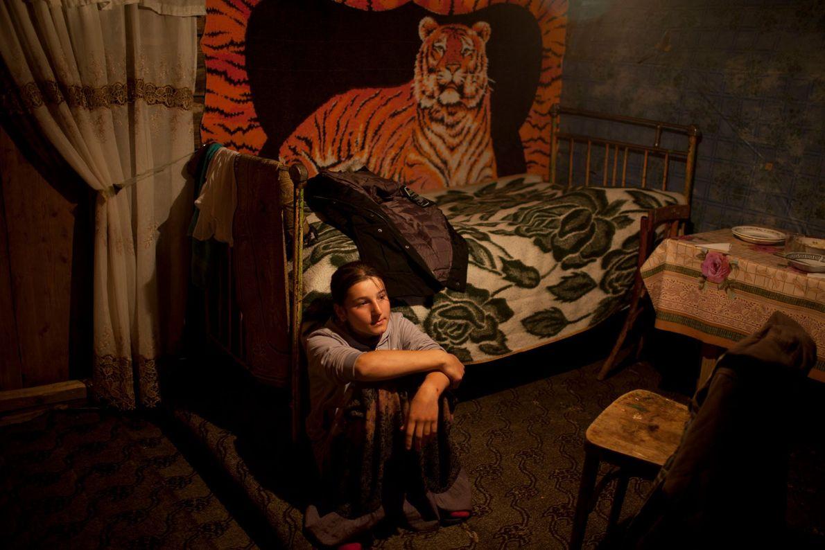 Imagem de uma rapariga sentada no seu quarto