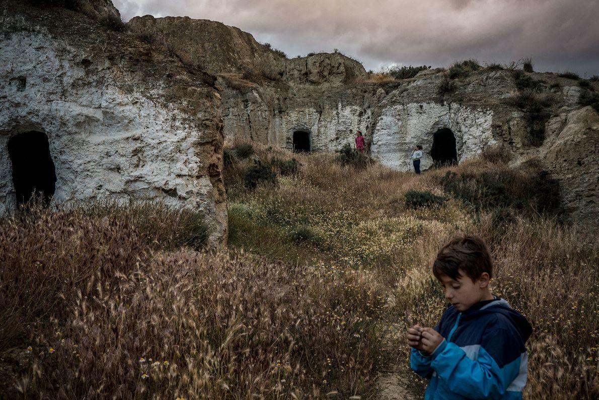 Um grupo de crianças brinca em grutas abandonadas, nas proximidades das grutas que lhes servem de ...