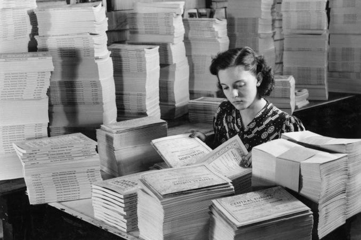 Uma jovem insere mapas entre as páginas de milhares de exemplares de uma revista na National ...