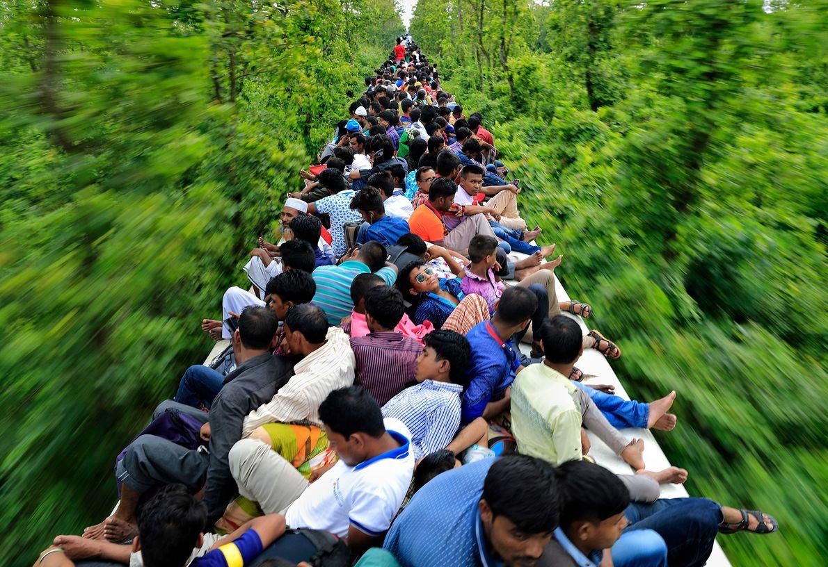 Fotografia de pessoas na parte de cima de um comboio no Bangladesh