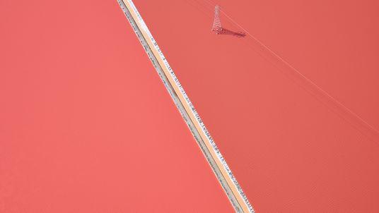 Fotografia de uma linha de electricidade a atravessar planícies de sal cor-de-rosa na Califórnia.