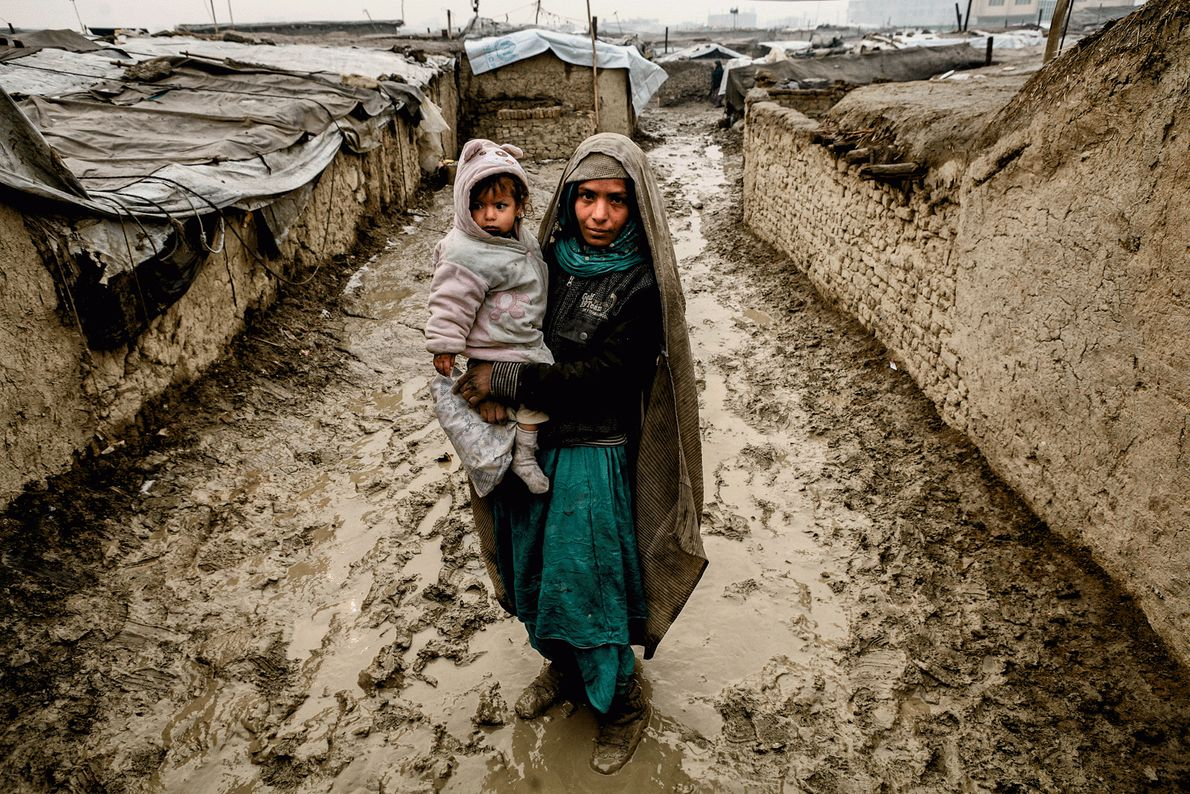 Imagem de uma mulher afegã internamente deslocada a segurar uma criança