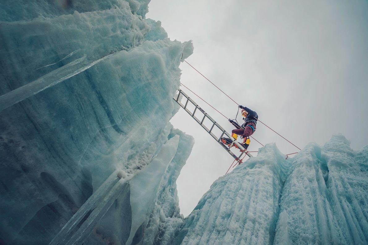 Imagem de uma mulher a atravessar uma fenda de gelo nos Himalaias