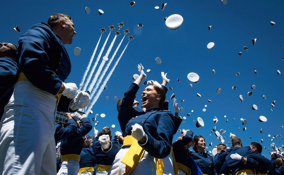 Fotografia de cadetes da Força Aérea American a atirar os seus bonés ao ar para celebrar ...