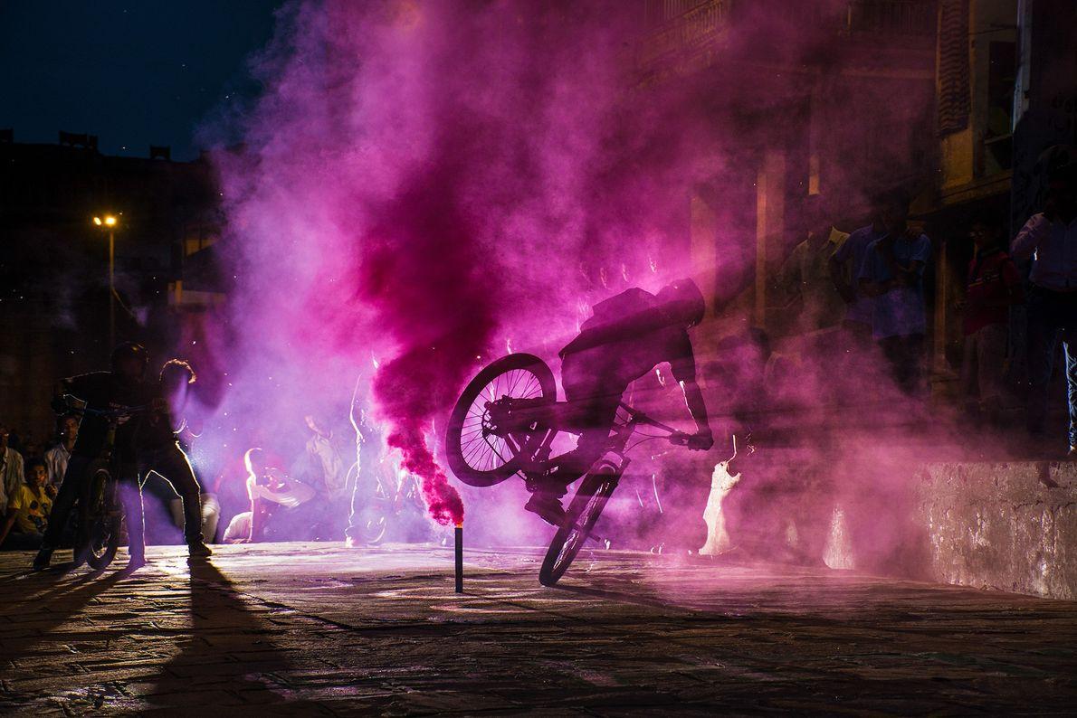 Fotografia de um ciclista a fazer um truque numa nuvem de fumo roxo