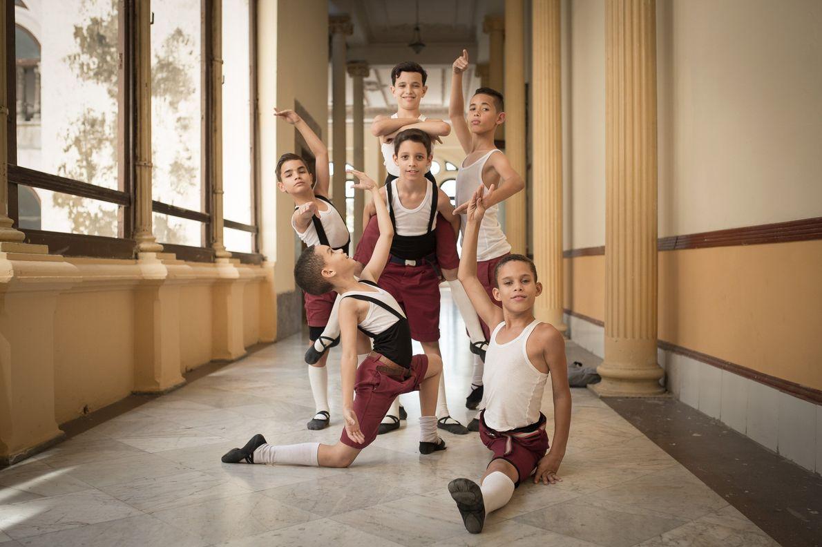 Fotografia de dançarinos masculinos, a pousarem numa sala da escola em Cuba
