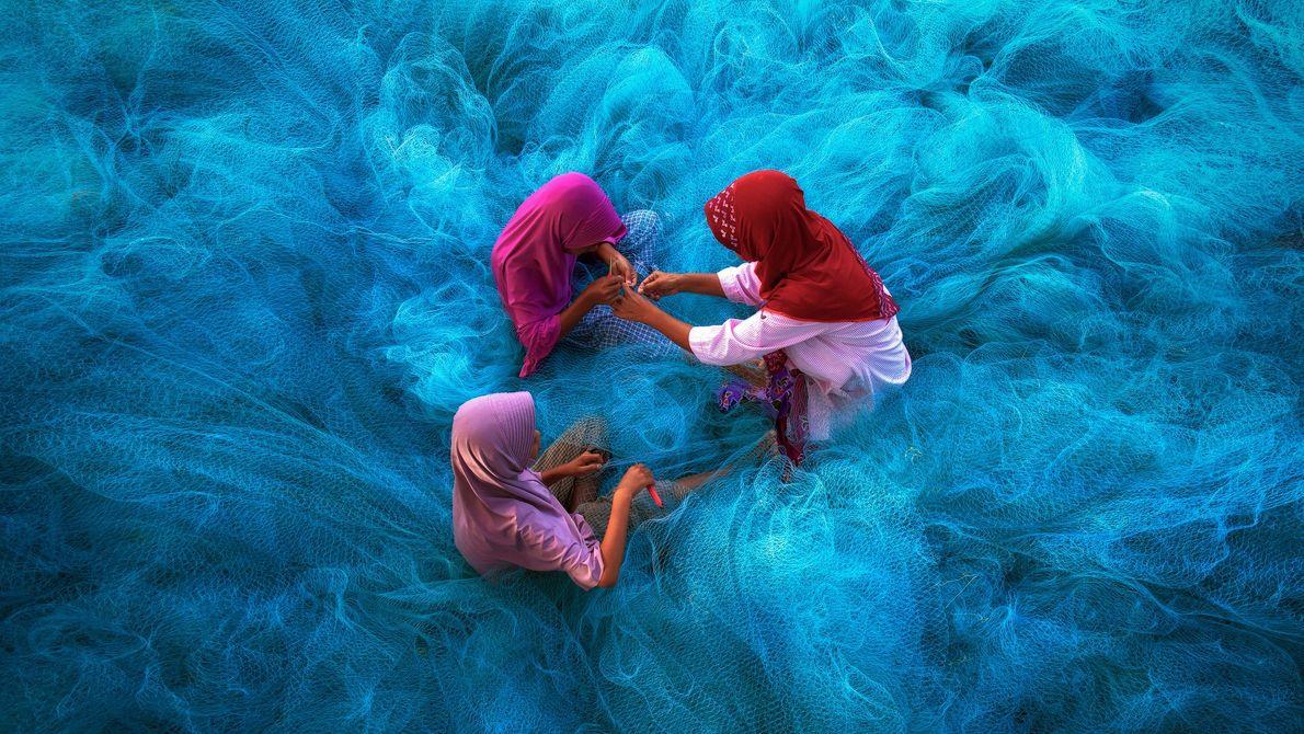 Fotografia de uma mãe e filhas a repararem redes de pesca azuis