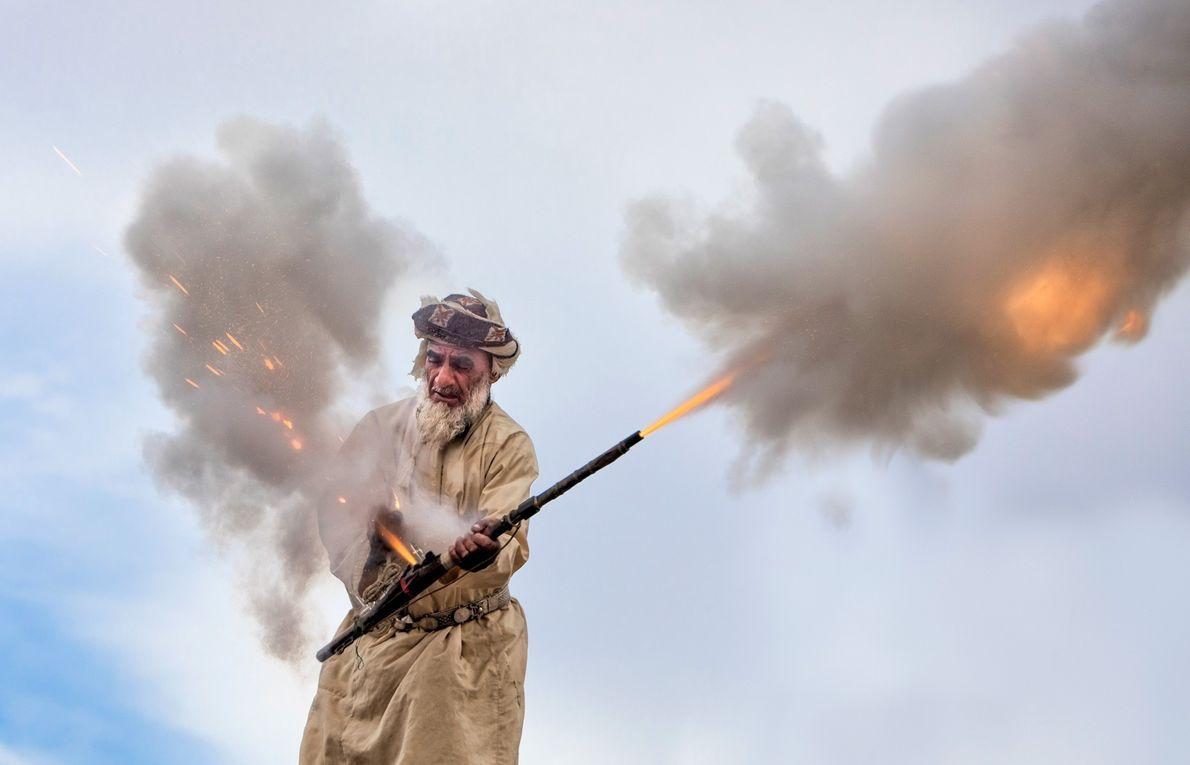 Fotografia de um homem a acender um canhão num casamento em Omã
