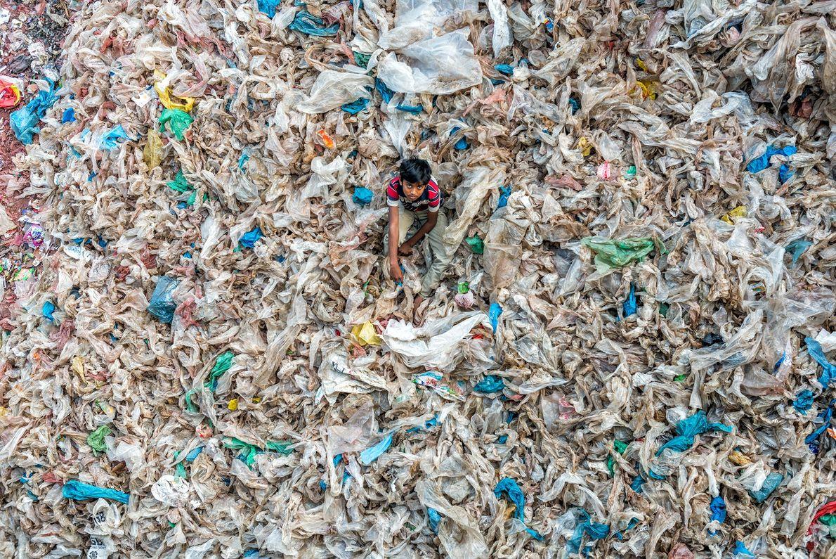 Fotografia de uma criança a brincar num monte de sacos de plástico sujos