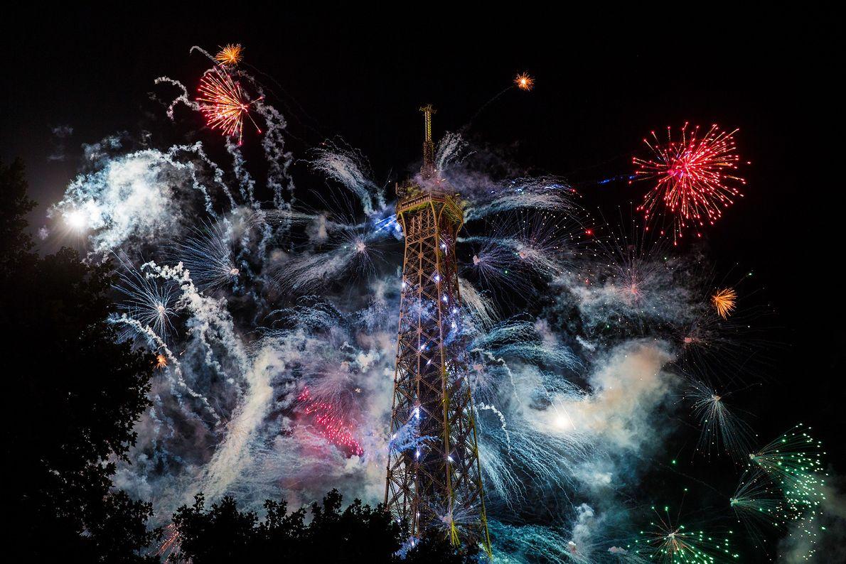 Fotografia de fogo de artifício a explodirem atrás da Torre Eiffel em Paris