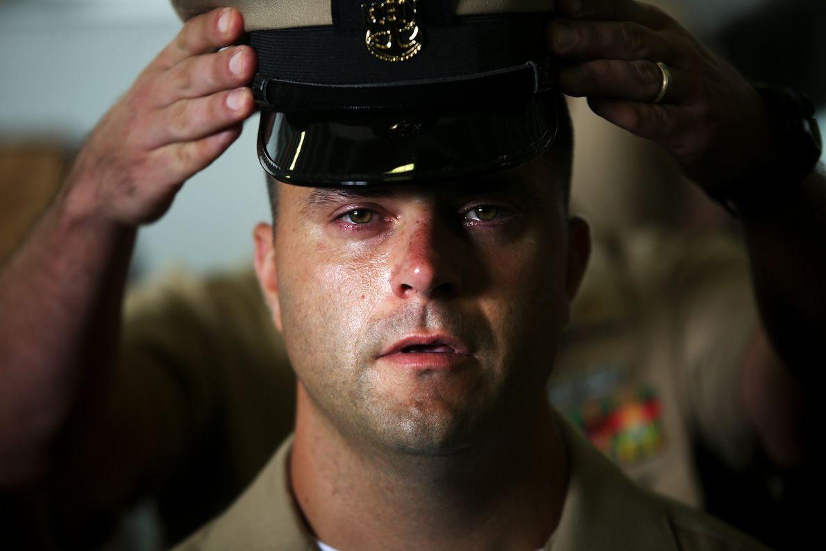 Fotografia de mãos a colocarem um chapéu militar na cabeça de um homem na Marinha dos ...