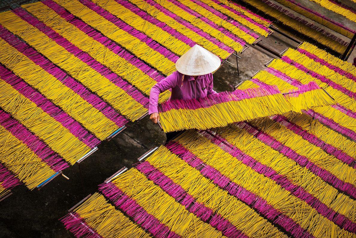 Fotografia de uma mulher a trabalhar com paus de incenso amarelos e rosa