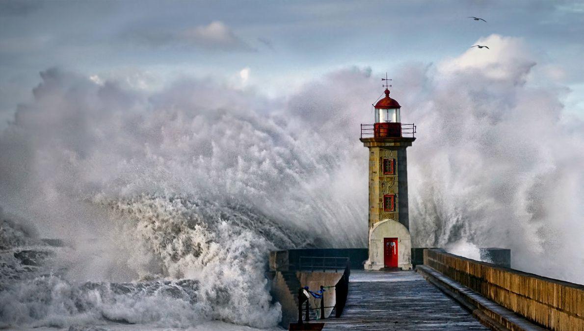 Fotografia de uma onda a embater num farol em Portugal