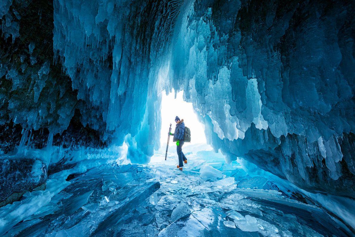 Fotografia de um alpinista em pé numa gruta de gelo