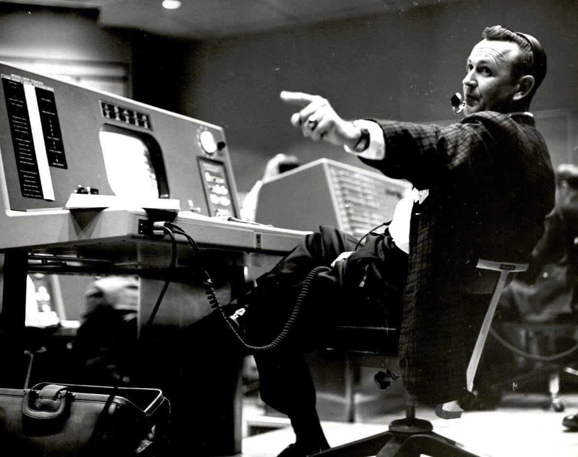 Christopher Kraft, diretor de voo do Programa Mercury, trabalha na sua consola na Área de Controlo ...