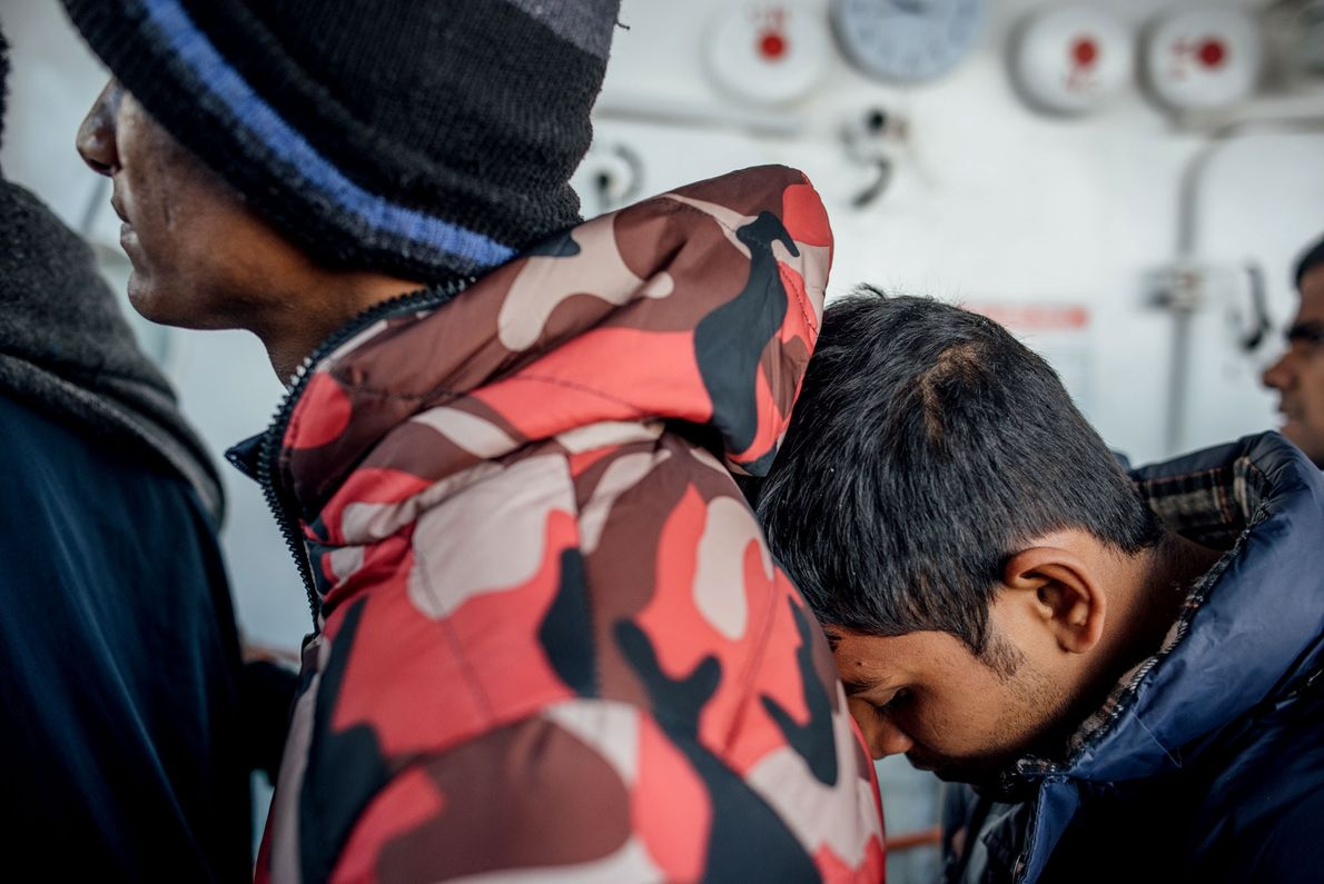 Refugiados salvos aguardam a vez na fila de distribuição de alimentos.