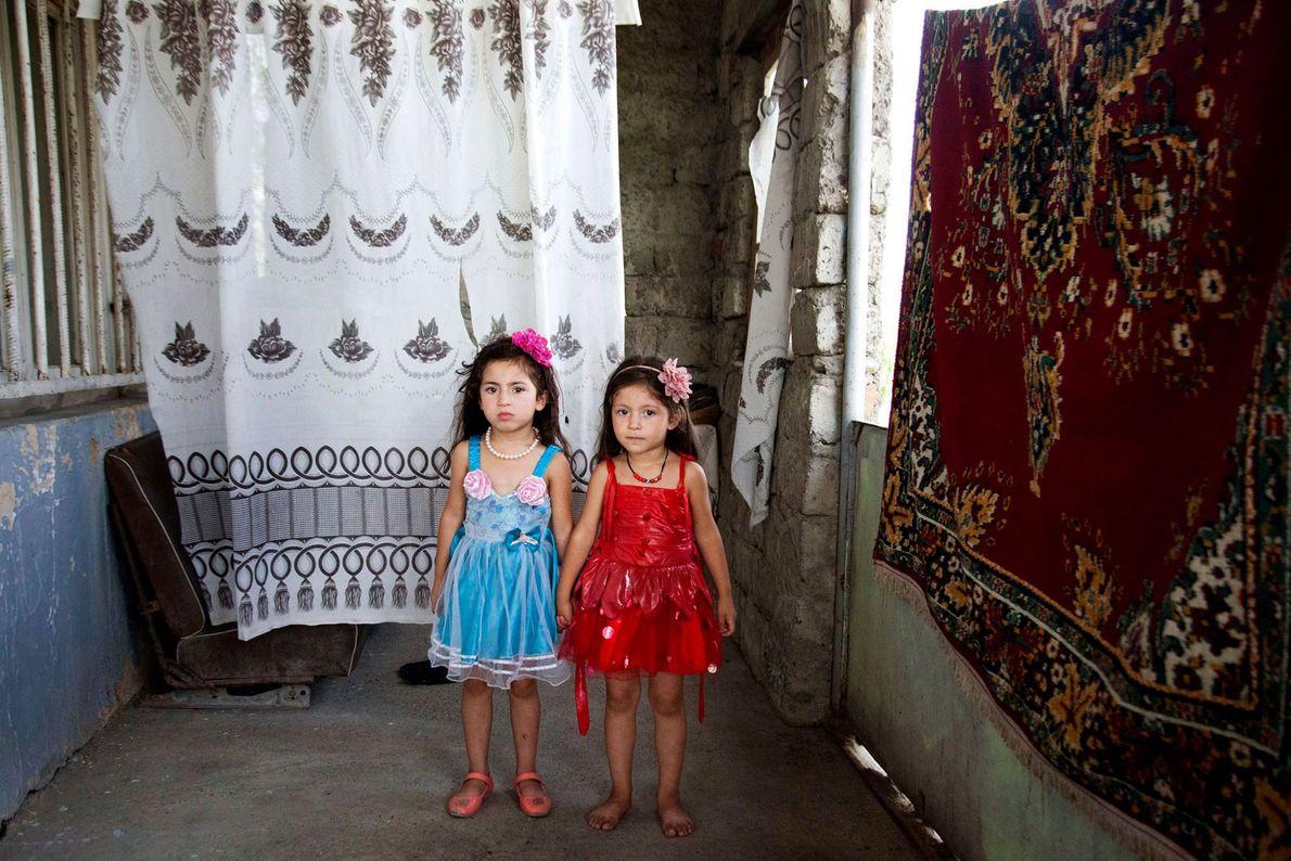 Imagem de duas irmãs gémeas a posarem à frente de um tapete