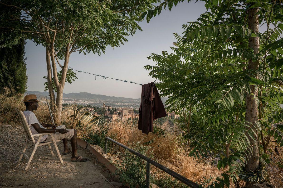 Sergine Mourtalla Mbacke, um imigrante senegalês, contempla a cidade de Granada e o palácio da Alhambra, ...