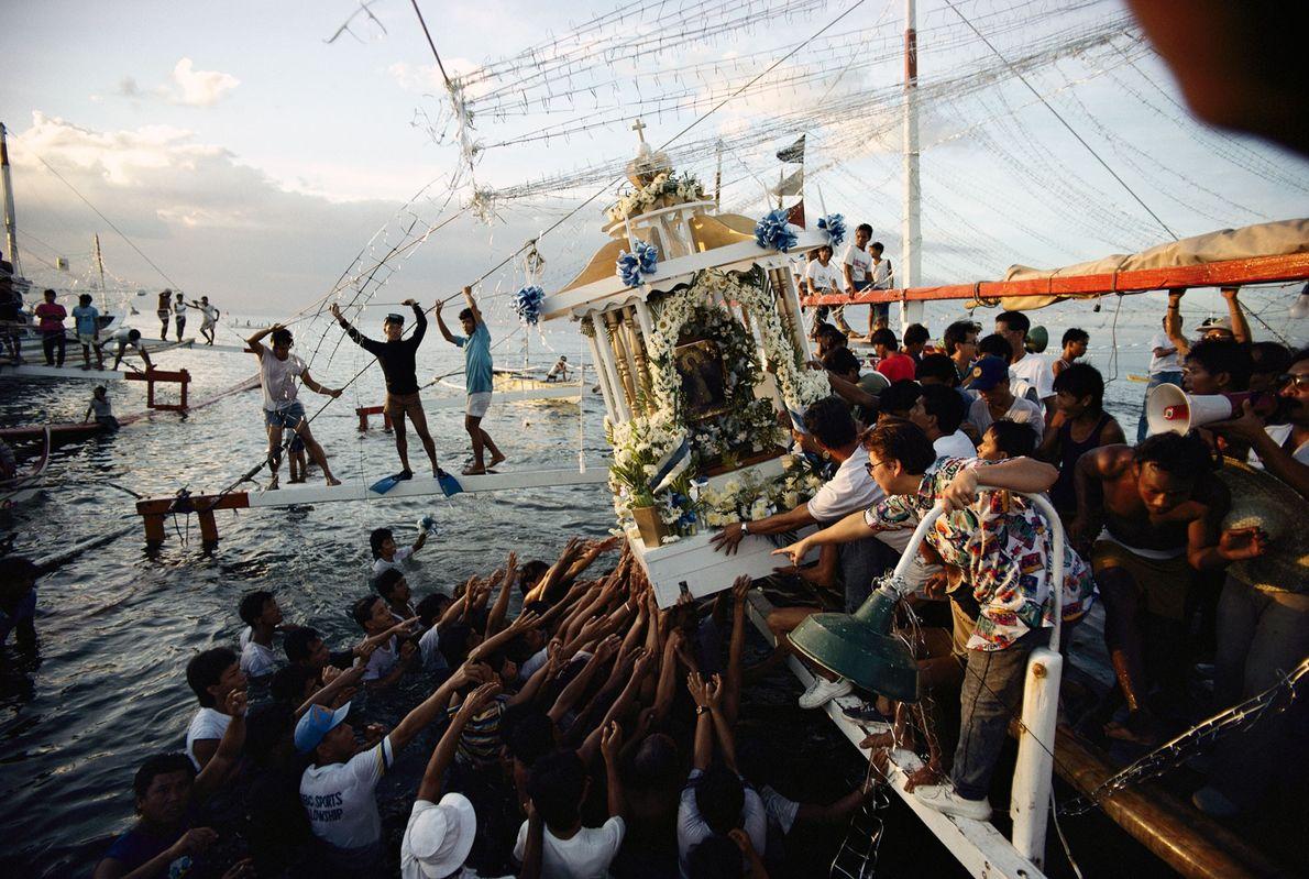 Nas Filipinas, fiéis transportam um palanquim com uma imagem religiosa.