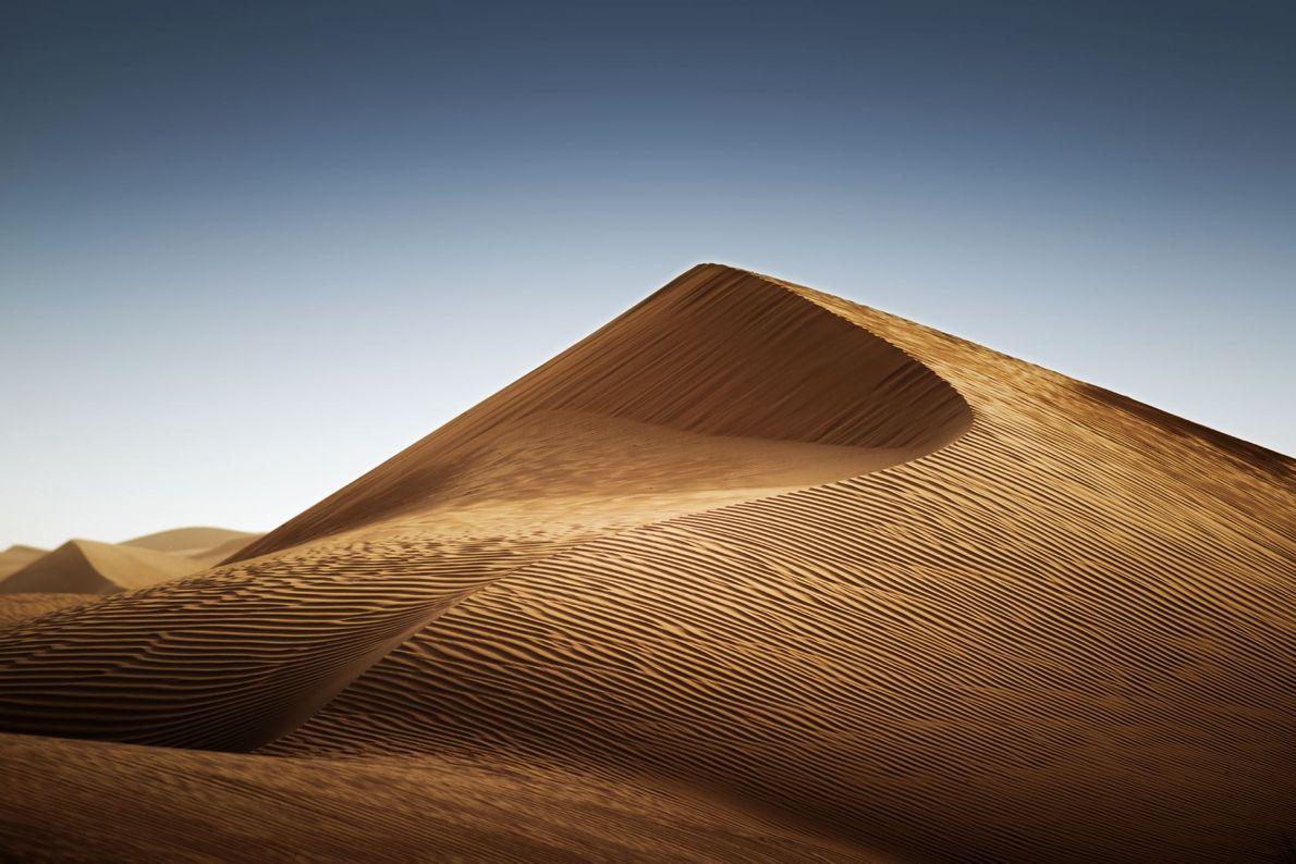 Fotografia de uma duna de areia alta texturada, com um céu azul no fundo, próximo do ...
