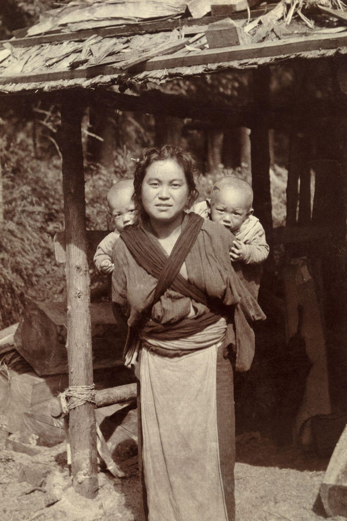 Uma mulher japonesa carrega dois gémeos às costas.
