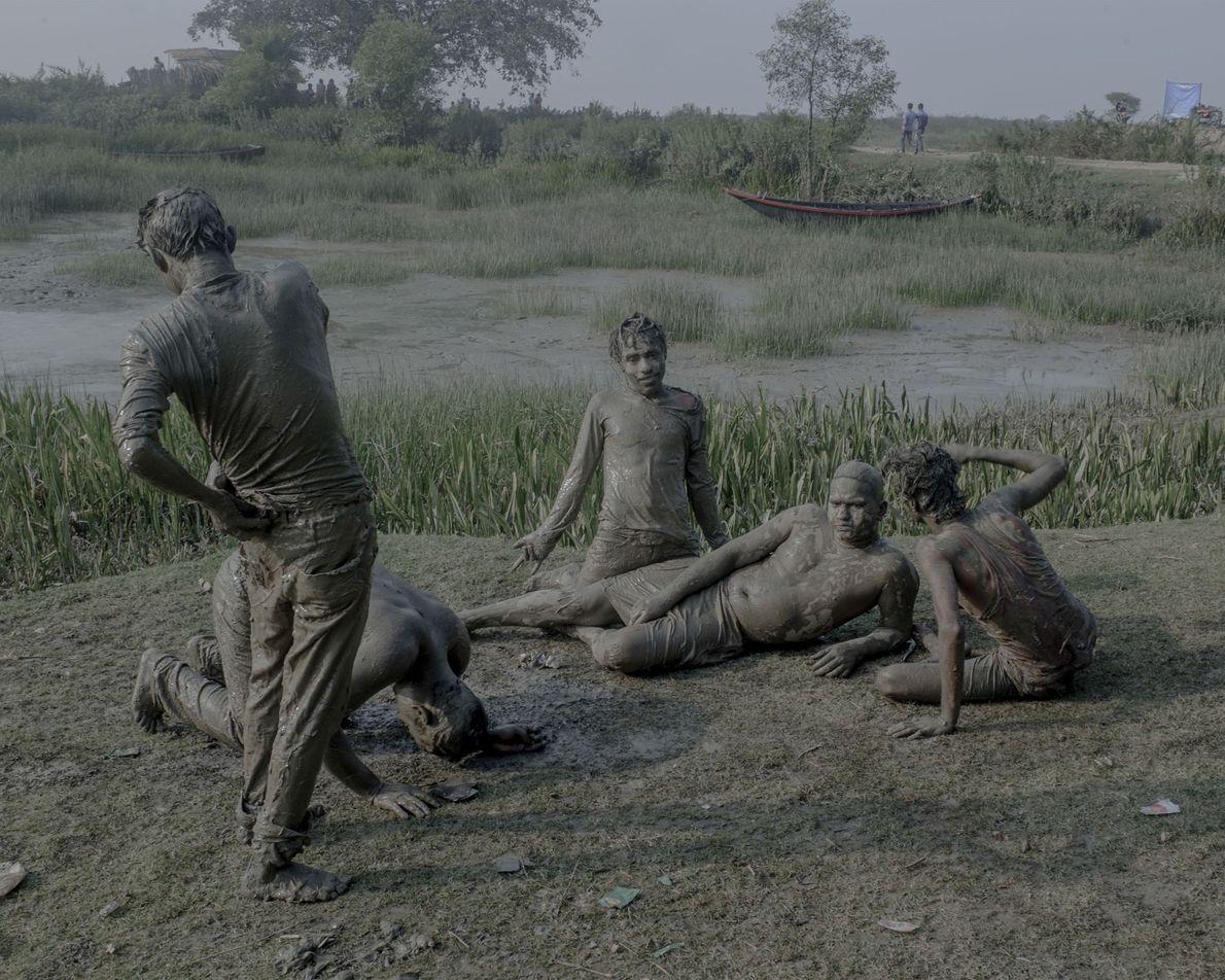 Jovens ébrios banham-se na lama das margens do rio Ganges.