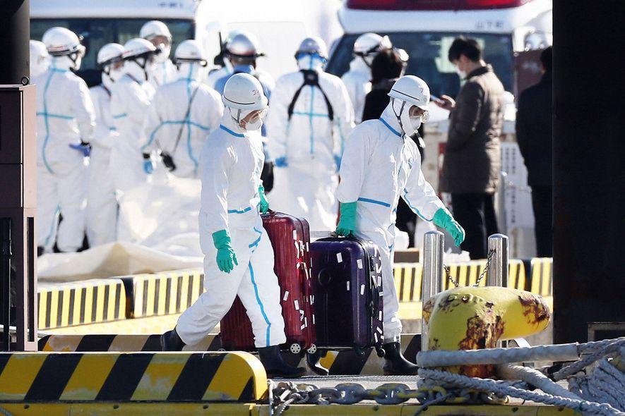 As autoridades de saúde, com equipamentos de proteção, removeram as bagagens do cruzeiro Diamond Princess, em ...