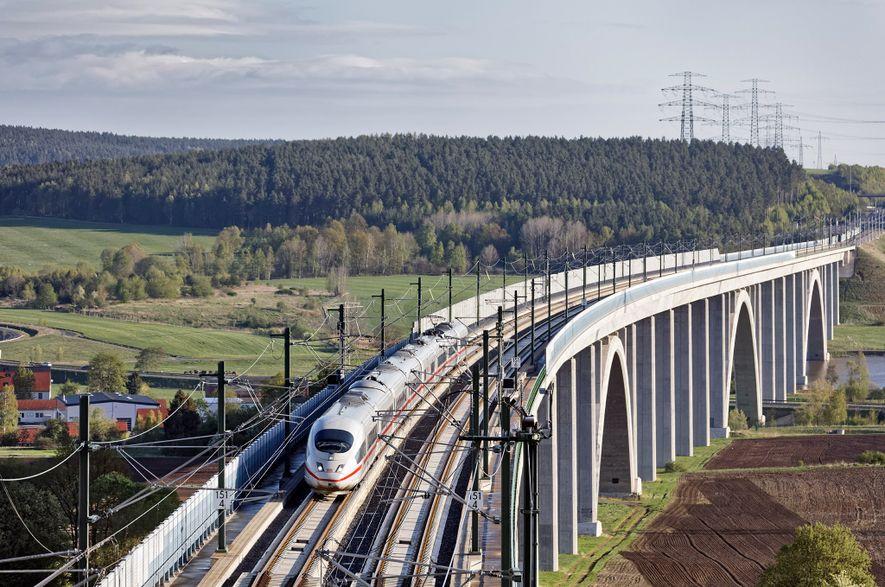 O comboio intercidades da Deutsche Bahn atravessa campos verdejantes.