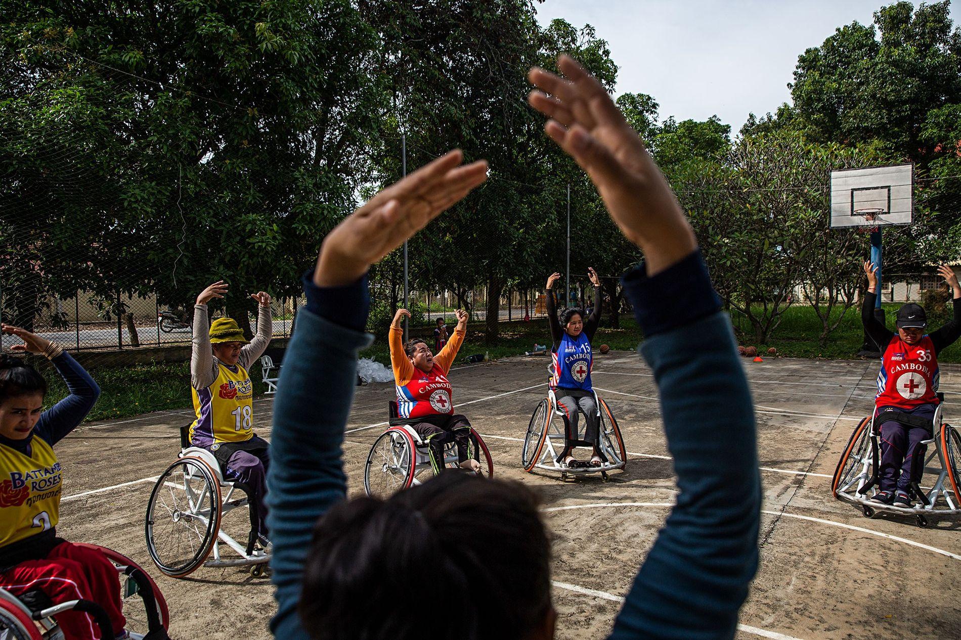 As Battambang Roses a fazerem alongamentos no campo de treinos do Centro Regional de Reabilitação.
