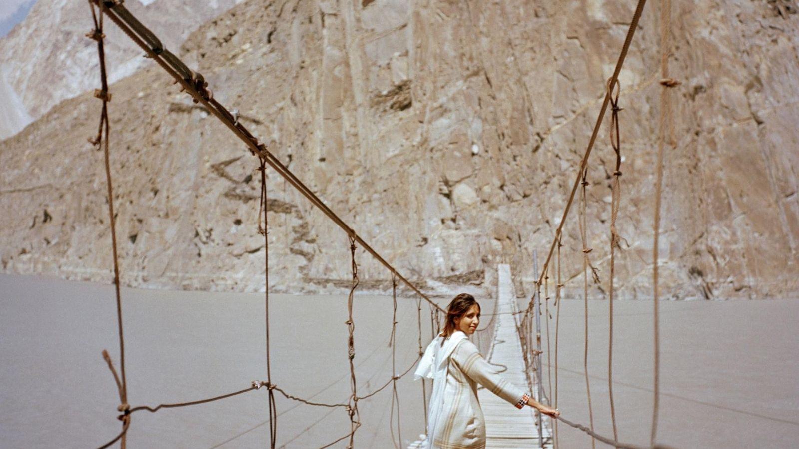 A visitante britânica Subeera Hussain caminha ao longo de uma ponte suspensa perto de Passu, uma ...