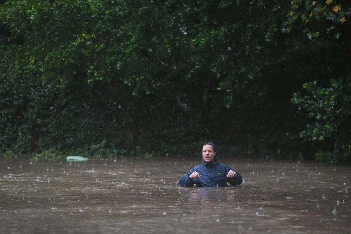 Um morador numa rua inundada