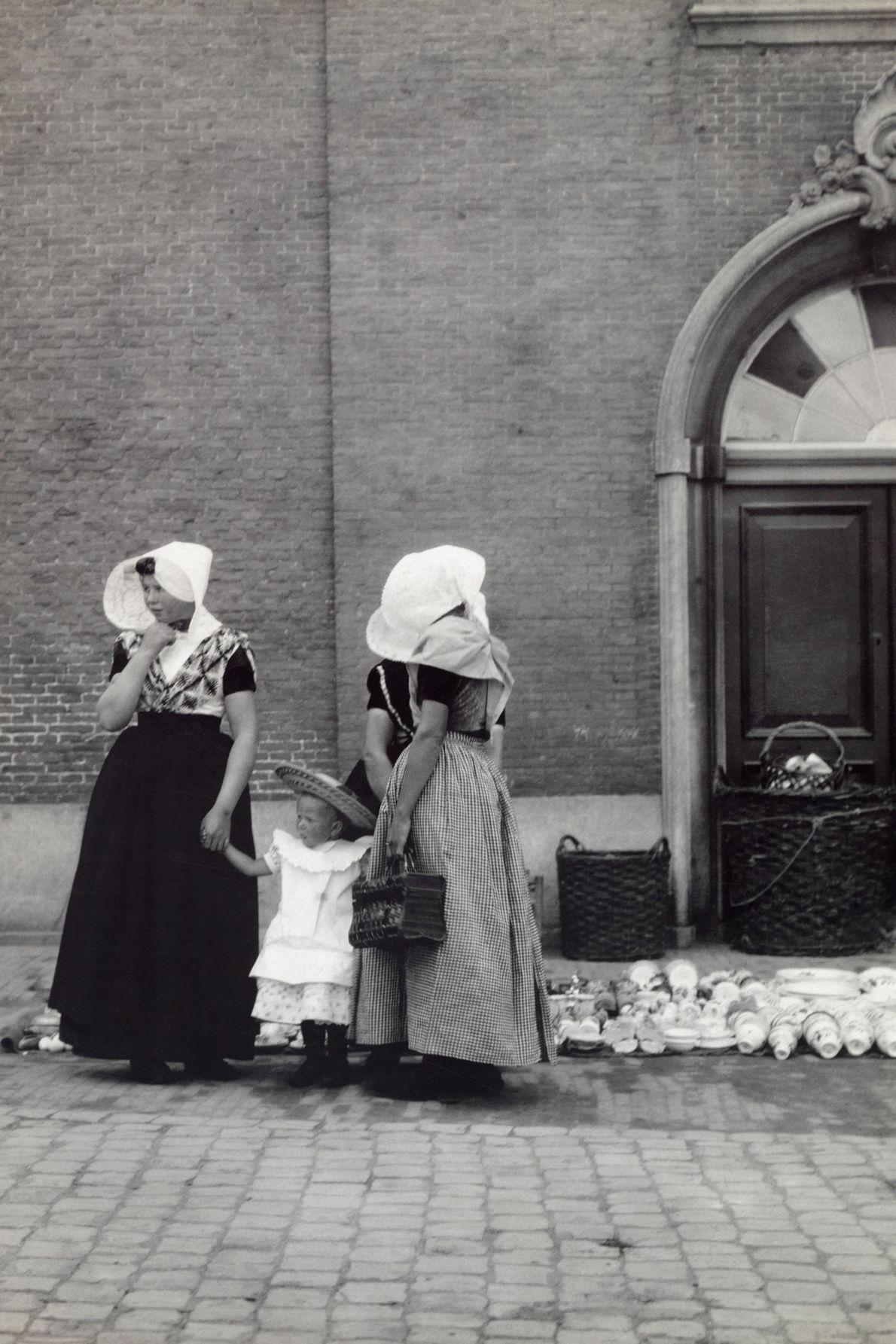 Uma criada e a sua senhora dão a mão a uma criança.
