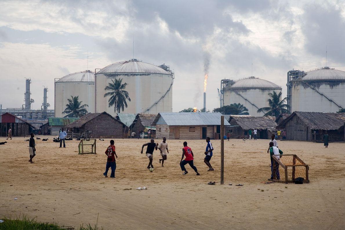 Jovens jogam futebol em frente de depósitos de gás.