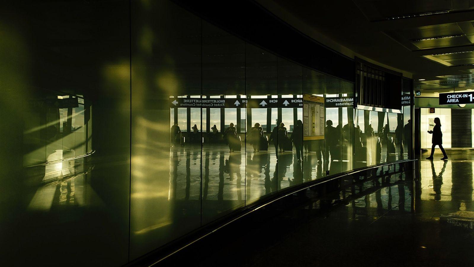 Viajantes aproximam-se das portas de embarque do Aeroporto Internacional de Malpensa de Milão, em Itália, em ...