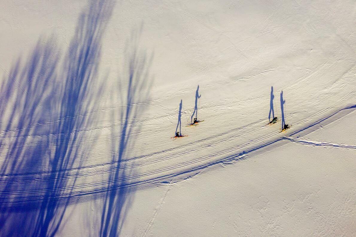 As árvores e os esquiadores projetam longas sombras na neve do Rikert Nordic Center em Ripton, ...