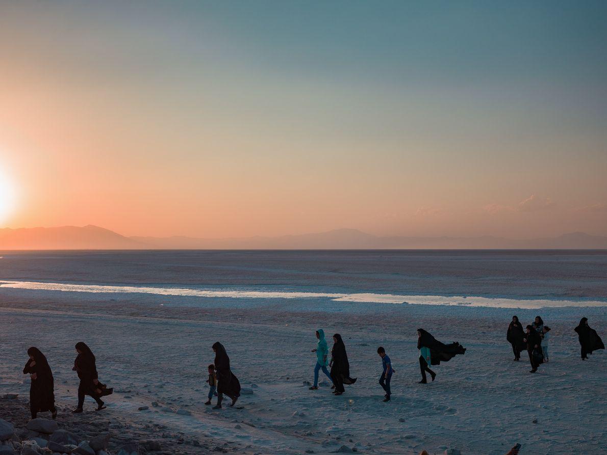 Família passeia na praia enquanto o sol se põe sob o Lago Urmia