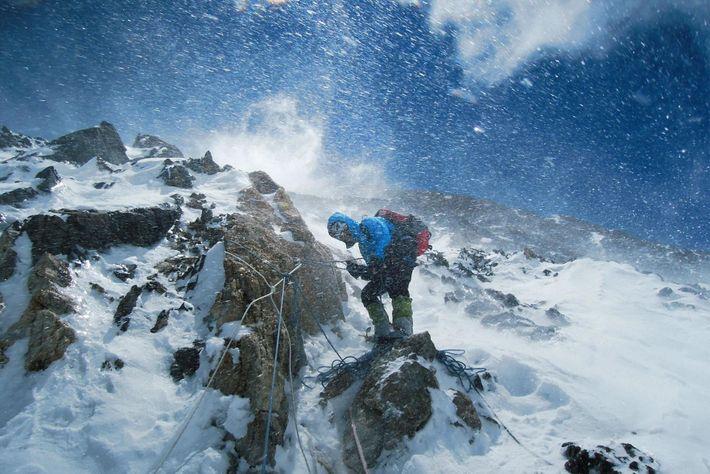 Fustigada por fortes rajadas de vento e neve, Gerlinde Kaltenbrunner verifica um segmento da corda.