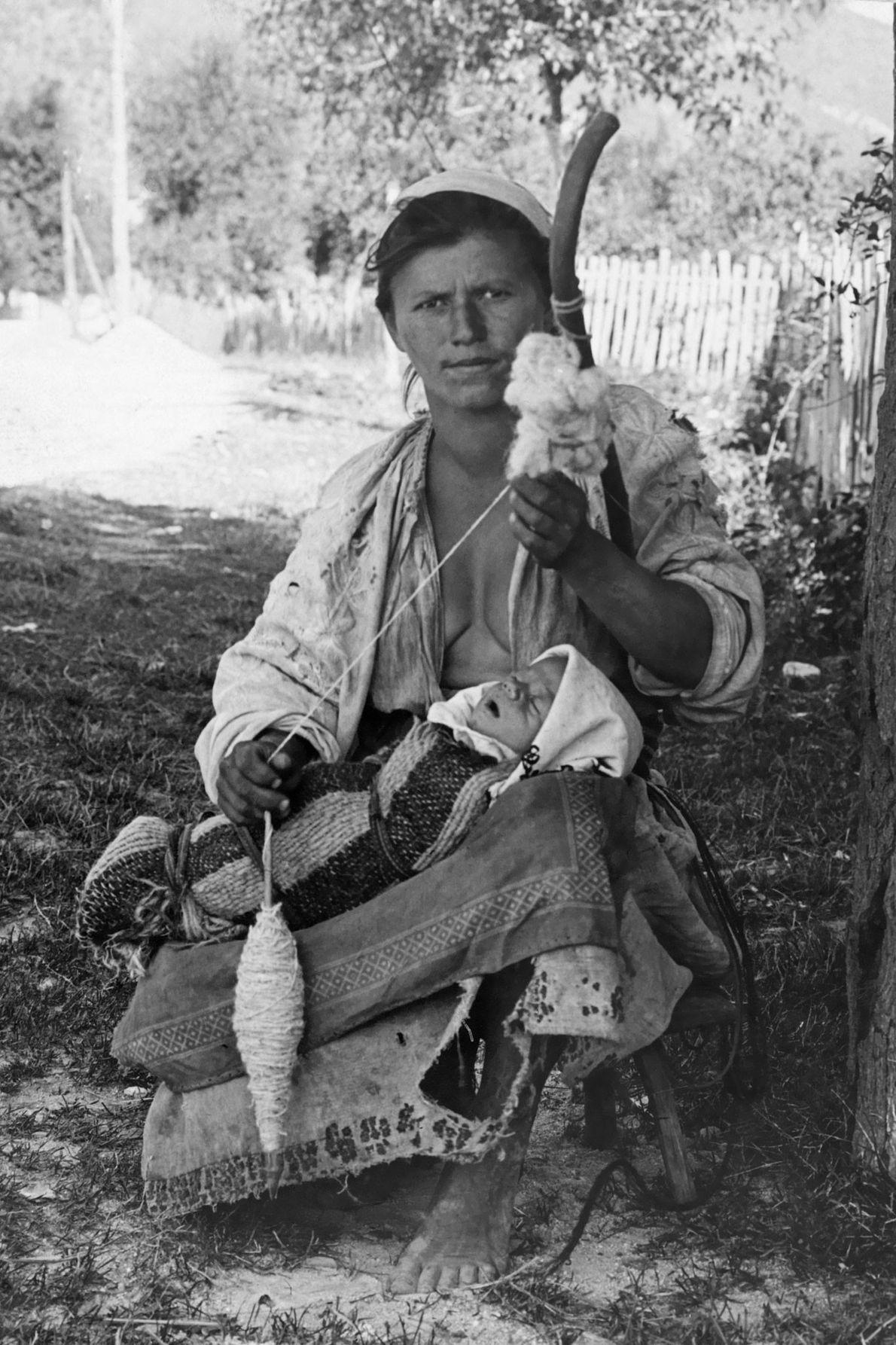 Uma mulher húngara fia lã, enquanto um bebé dorme.