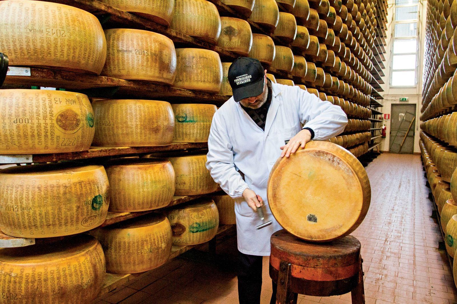 Em Itália, um graduador mestre do consórcio Parmigiano-Reggiano, testa a qualidade de uma roda do famoso ...