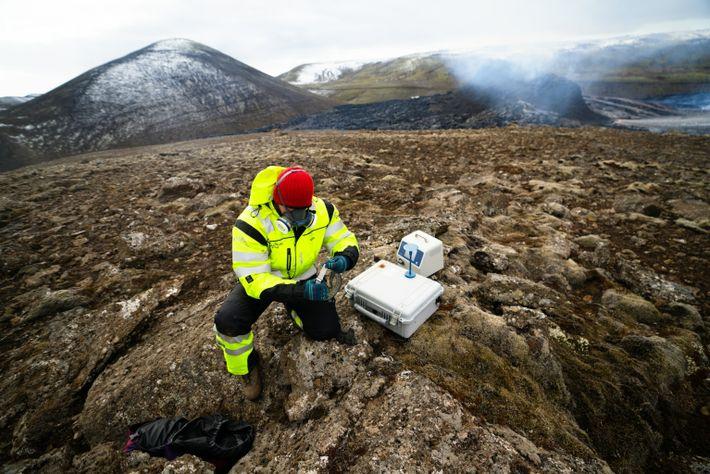 Um membro da equipa de Busca e Salvamento da Islândia (ICE-SAR) mede os níveis de gás ...