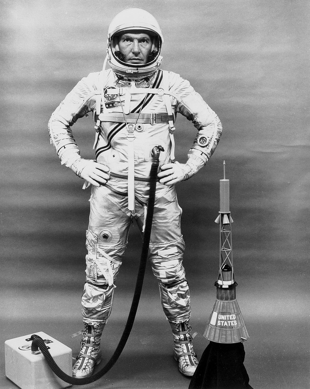 Wally Schirra posa com o seu fato, kit de oxigénio portátil e um modelo da cápsula ...