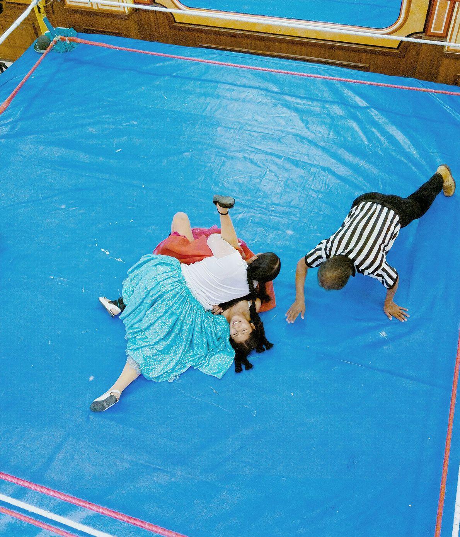Duas mulheres lutam sob o olhar de um árbitro.