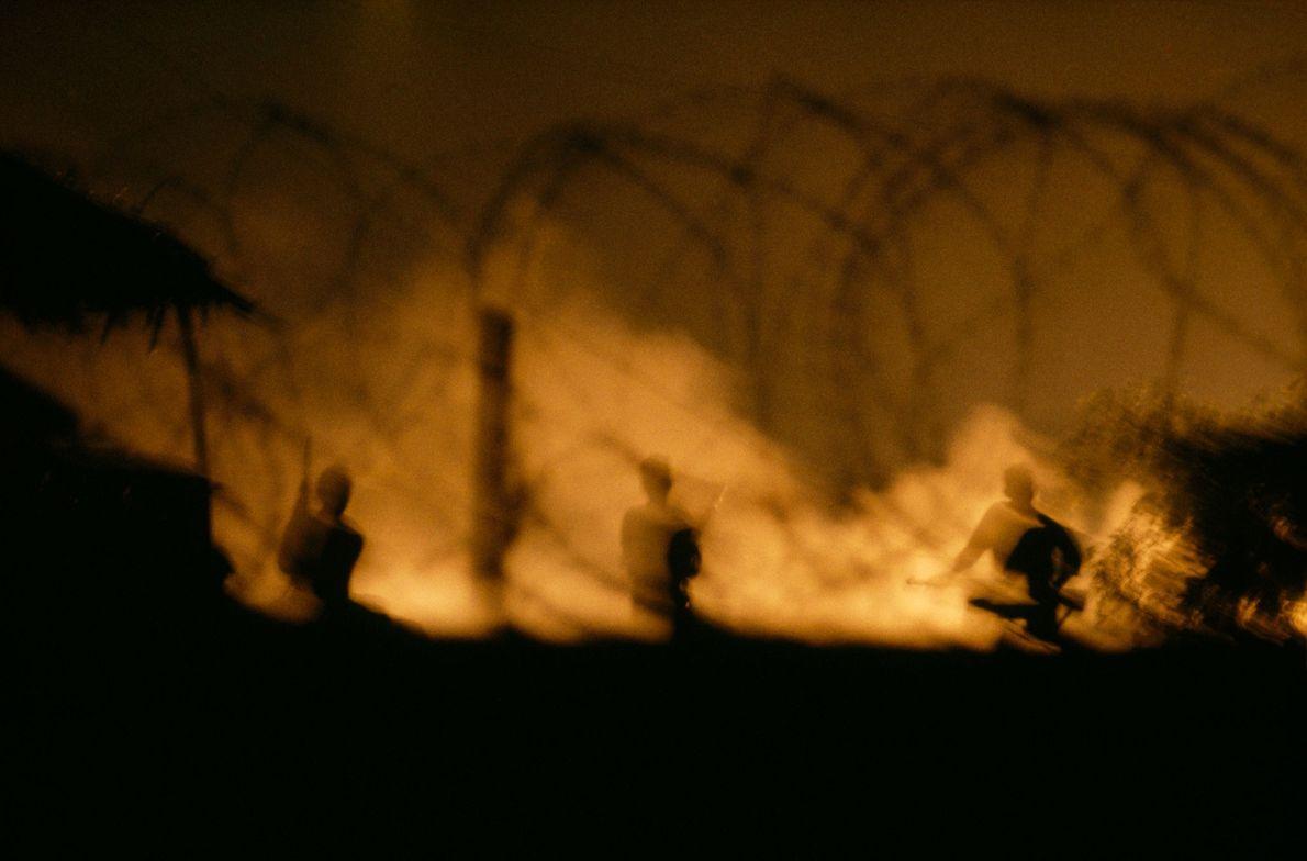 Um inferno flamejante ilumina os soldados vietcongues, no delta do rio Mekong, no Vietname do Sul.