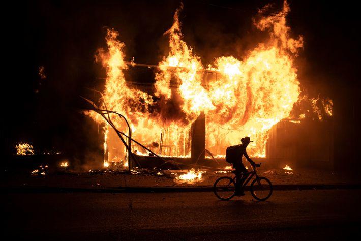 Um manifestante passa de bicicleta em frente a um prédio que ficou em chamas durante os ...