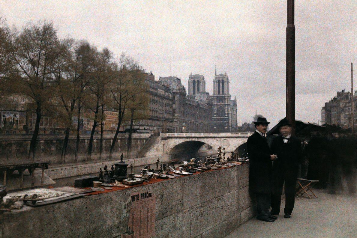 Dois homens junto a uma venda de bugigangas, nas margens do Rio Sena, nos anos 1920, ...