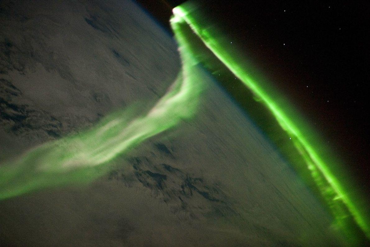 Nesta fotografia, tirada em 2010 por um astronauta na Estação Espacial Internacional, um fluxo verde néon ...
