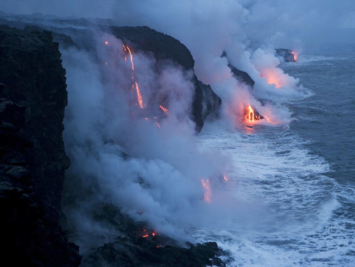 Uma escoada de lava precipita-se sobre o oceano Pacífico no Parque Nacional dos Vulcões Havaianos.