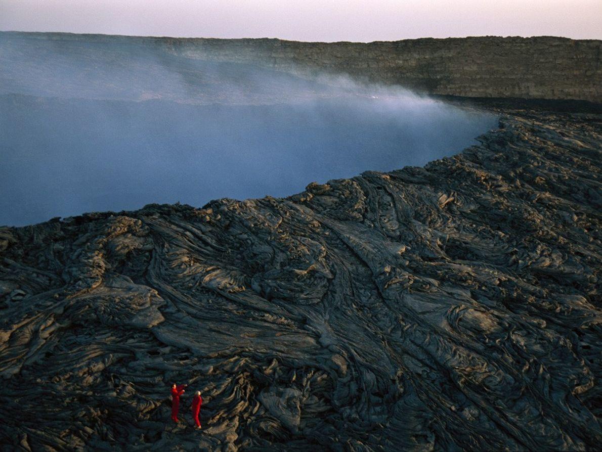 Alpinistas caminham sobre espirais de lava na caldeira do vulcão de Ertale, na Etiópia.